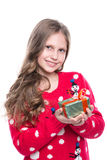 Charming smiling little girl with curly hairstyle wearing red knitted sweater and holding christmas gift isolated on white. stock photos