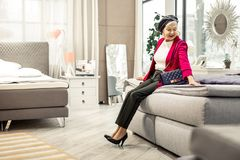 Charming smiling modish dame trying new bed in showroom. Buying new bed. Charming radiantly smiling modish dame wearing leather cap, trendy pink blazer and royalty free stock image