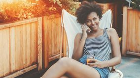 Afro girl with glass of drink in street cafe Royalty Free Stock Photo