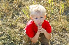 Charming smudgy little boy with big eyes. In the squatting position, back-light Royalty Free Stock Images