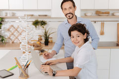 Charming son and his father doing a school project together. Pleasant working atmosphere. Handsome pleasant boy sitting at the kitchen counter, holding hands on Stock Photo