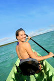Charming sportive woman rowing in canoe. Back view of beautiful woman paddling in canoe stock image