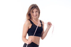 Charming sports girl who is smiling and holding a measuring tape Royalty Free Stock Images