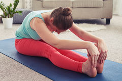 Charming sportswoman practicing yoga in seated forward bend pose Stock Image