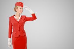 Charming Stewardess Dressed In Red Uniform On Gray Background. Stock Photo