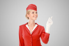 Charming Stewardess Dressed In Red Uniform Pointing The Finger. On Gray Background royalty free stock photography