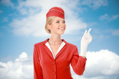 Charming Stewardess Dressed In Red Uniform Pointing The Finger. Sky With Clouds Background stock photography