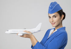 Charming Stewardess Holding Airplane In Hand. Royalty Free Stock Photo