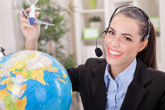Charming Stewardess Holding Airplane In Hand,traveling or tourism concept. Young smiling support phone operator with the airplane in hand and the globe royalty free stock image