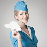 Charming Stewardess Holding Paper Plane In Hand. Gray Background Stock Photo