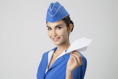 Charming Stewardess Holding Paper Plane In Hand. Gray Background Stock Photos
