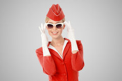 Charming Stewardess In Red Uniform And Vintage Sunglasses. Charming Stewardess Dressed In Red Uniform And Vintage Sunglasses On Gray Background stock images