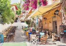 Charming street in the old district of Plaka in Athens, Greece. Beautiful street with cafe tables in Athens, Greece Royalty Free Stock Photos