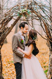 Charming stylish wedding couple softly hugging under romantic hazel arch in  autumn forest Royalty Free Stock Image