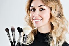 Charming stylist holds four professional brushes for applying ma stock photo