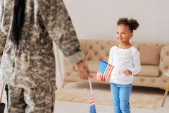 Charming sweet child greeting her mom. Finally home. Excited lively young girl waiting for her moms return in a living room while holding a flag and looking stock photography