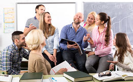 Charming teacher and his students. Charming language teacher is telling interesting stories to his attentive students during a break in a classroom Stock Photos