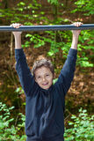 Charming Teenage Boy. In a forest, hanging on his arms from a chin up bar Royalty Free Stock Photo