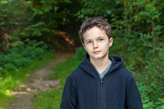 Charming Teenage Boy. Standing in a forest, looking into the camera Royalty Free Stock Images