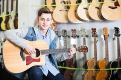 Charming teenage customer deciding on acoustic guitar Royalty Free Stock Image