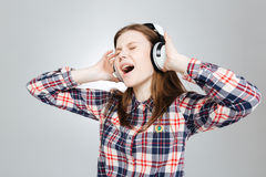 Charming teenage girl listening to music and singing Stock Images