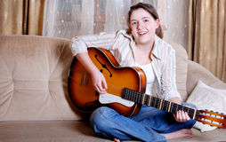 Charming teenage girl play by guitar Stock Photography