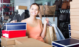 Charming teenager female holding boxes in shoes boutique Royalty Free Stock Photos