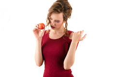 Charming teenager girl in red dress with nectarine in hand Stock Image