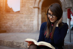 Charming teenager sitting outdoors with open book. Portrait of a female university student reading interesting book on campus, charming teenager sitting outdoors Royalty Free Stock Images