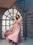 Charming tender princess in long peach pink shiny satin flying waving dress with neckline, girl stands on vintage stairs. And looks down, evening lady image on stock image