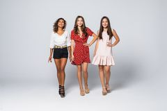 Charming three beautiful multiethnic young adult friends with dresses smiling and looking at camera isolated on white wall. Studio royalty free stock images