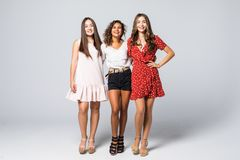 Charming three beautiful multiethnic young adult friends with dresses smiling and looking at camera isolated on white wall. Studio stock images