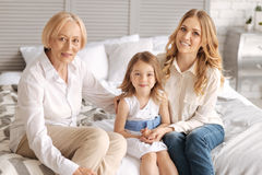 Charming three generations of women bonding. Enjoying themselves. Grandmother, mother and her little daughter sitting on the bed and bonding to each other, while Royalty Free Stock Photo