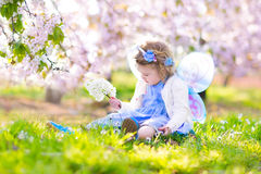 Charming toddler girl in fairy costume in fruit garden. Adorable toddler girl with curly hair and flower crown wearing a magic fairy costume with a blue dress Stock Images