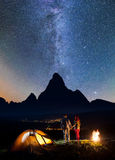 Charming tourist couple - girl and guy holding hands, standing near fire and enjoying incredibly beautiful starry sky Royalty Free Stock Photo