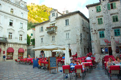 Charming town square in Kotor, Montenegro. Red chairs brighten a charming town square in the coastal town of Kotor, Montenegro. Tourists gather her to dine al Stock Image