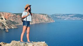 Charming travel backpacker woman standing on top of mountain admiring beautiful sea landscape. View full shot. Female tourist wearing hat and sunglasses having stock video footage