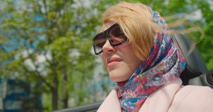 Charming trendy woman with natural make-up in sunglasses and scarf on her hair is driving in cabriolet. Moving hair from. Wind. 4k footage stock video footage