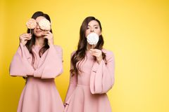 Charming twins closing eyes with lollipops and posing. Front view of charming twins in pink dresses closing eyes with lollipops and posing on isolated background royalty free stock photography