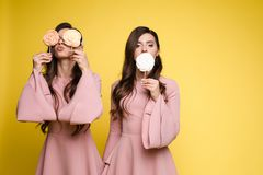 Charming twins closing eyes with lollipops and posing. Front view of charming twins in pink dresses closing eyes with lollipops and posing on isolated background stock photo