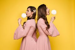 Charming twins eyes with lollipops and posing. Front view of charming twins in pink dresses closing eyes with lollipops and posing on isolated background. Two royalty free stock photography