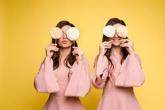 Charming twins eyes with lollipops and posing. Front view of charming twins in pink dresses closing eyes with lollipops and posing on isolated background. Two stock photos