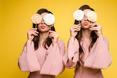 Charming twins eyes with lollipops and posing. Front view of charming twins in pink dresses closing eyes with lollipops and posing on isolated background. Two royalty free stock photos