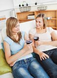 Charming two women drinking wine sitting on a sofa Royalty Free Stock Photography
