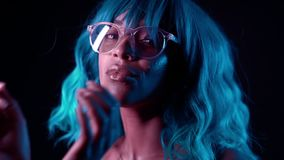 Charming unusual girl with blue hairstyle corrects her glasses. Sexy woman with perfect makeup and wig looking at camera