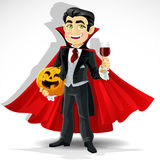 Charming vampire with Halloween pumpkin Stock Photos