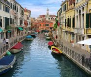 Charming Venetian canal street with colorful boats Royalty Free Stock Photo