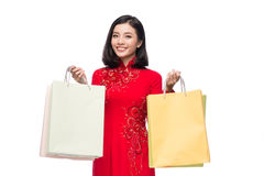 Charming Vietnamese Woman in Red Ao Dai Traditional Dress holding Shopping Bags. stock photography