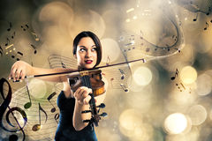Charming violinist. Elegant woman playing the violin with background of a stave with musical notes Stock Image