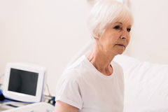 Charming vulnerable aged woman sitting up in hospital bed Royalty Free Stock Photo